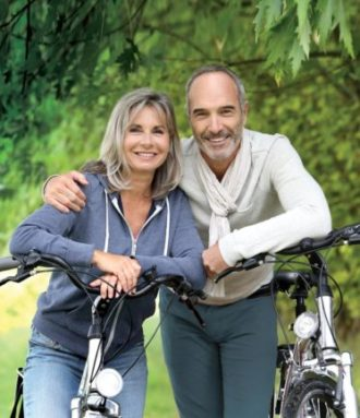 a happy mature couple pose while out for a bike ride in the park