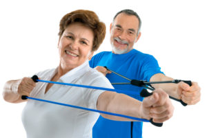 A mature couple smiling while exercising their upper body with resistance bands
