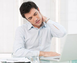 a young business man sitting at his desk is rubbing his sore neck.