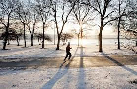 A man is running on a road through a winter sunrise