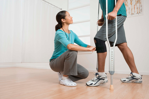 this is an image of a young black physiotherapist working a male client with crutches and a knee brace